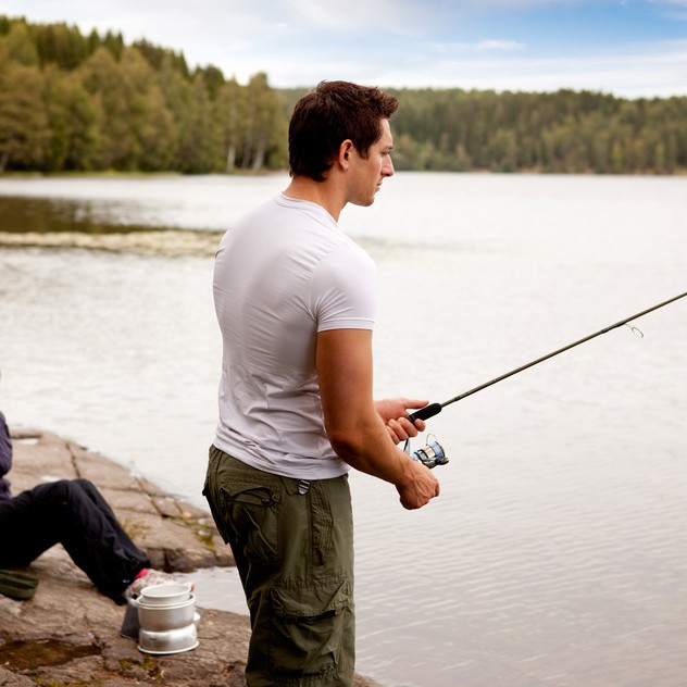 A man fishing on a lake with camping equipment and woman in background